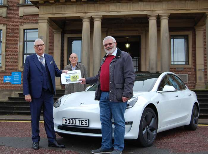 Stephen Brown (left) receiving his private hire plates from Coun Colin Hartley, chair of the council's licensing committee, watched on by Coun Kevin Frea, deputy leader.